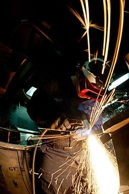 Worker using a plasma cutter
