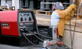 Worker using engine driven welders