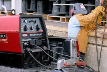 Worker using engine driven welders
